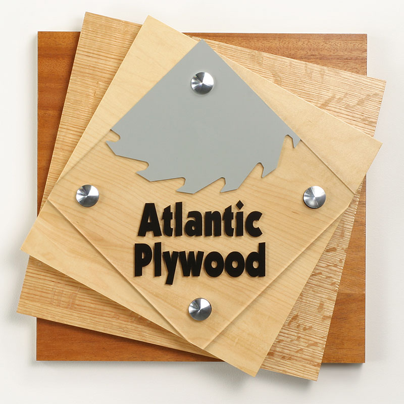 Standoffs supporting a stacked wood sign with company logo