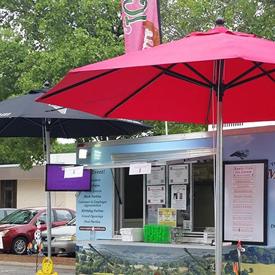 Food truck shown with large patio umbrellas